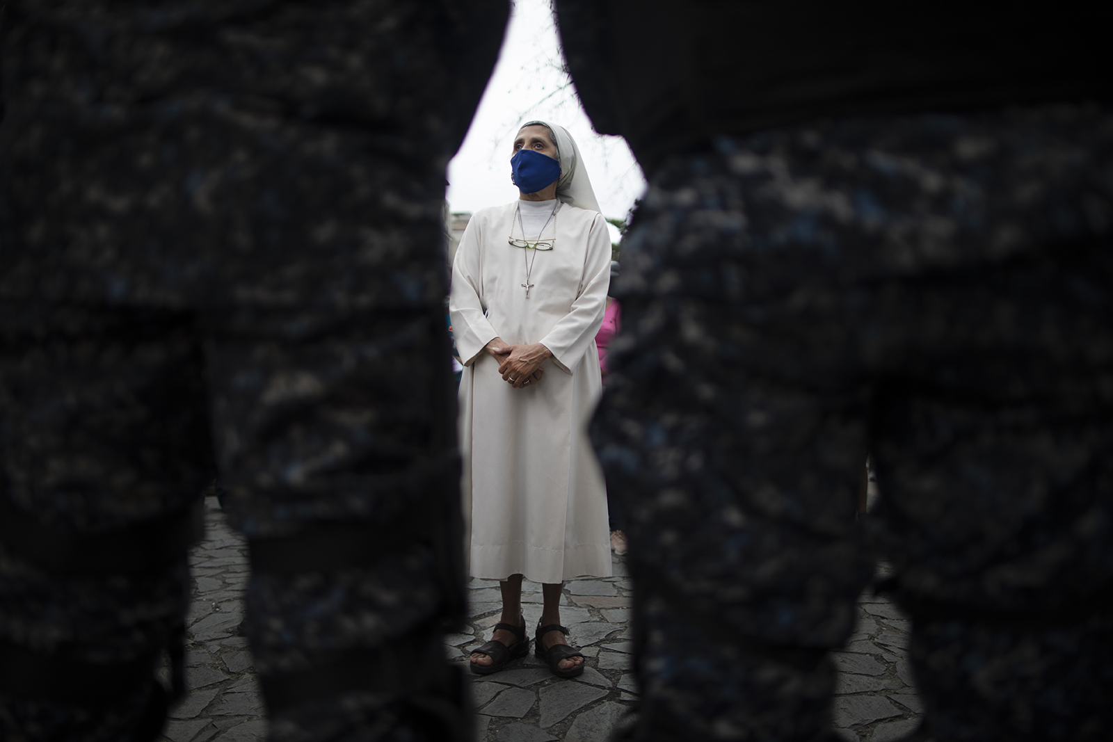 """A nun stands behind police creating a perimeter for a Holy Week procession by devotees of the """"Nazareno de San Pablo"""" statue of Jesus before it passes through in a popemobile amid the COVID-19 pandemic in Caracas, Venezuela, Wednesday, March 31, 2021. The annual procession wasn't allowed for the second year in a row to help contain the spread of the new coronavirus. (AP Photo/Ariana Cubillos)"""