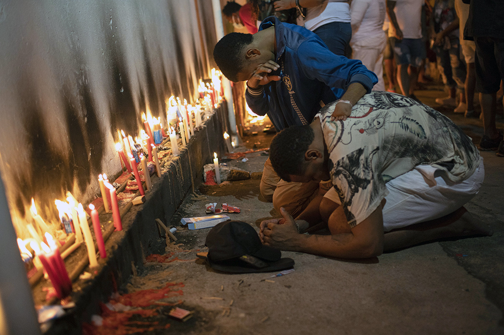 People pray by burning candles on the feast day of Saint George outside Saint George Church, closed to help contain the spread of COVID-19, in Rio de Janeiro, Brazil, before sunrise, Friday, April 23, 2021. The Catholic saint is associated with bravery and resistance. (AP Photo/Silvia Izquierdo)