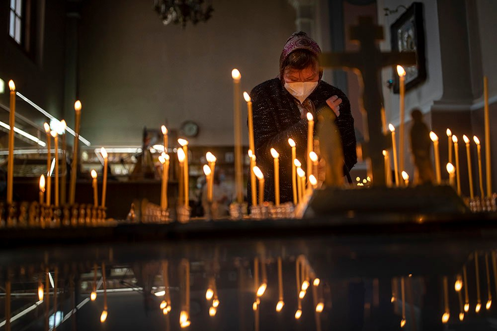 A Lithuanian Orthodox woman prays and lights candles during the Palm Sunday Mass at the Orthodox Church of the Holy Spirit in Vilnius, Lithuania, Saturday, April 24, 2021. Orthodox Christians will celebrate Easter on Sunday, May 2, 2021. (AP Photo/Mindaugas Kulbis)
