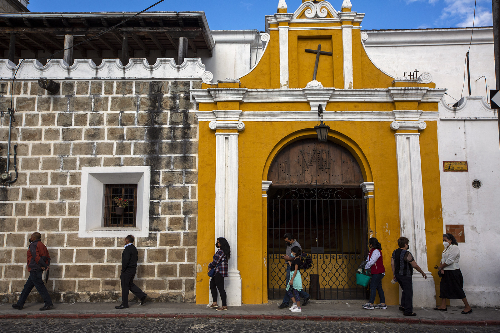 Neighbors walk past a Via Crucis station during holy week amid the COVID-19 pandemic in Antigua, Guatemala, Thursday, April 1, 2021. The traditional Easter processions have been canceled in Guatemala as a measure to contain the spread of the new coronavirus. (AP Photo/Moises Castillo)