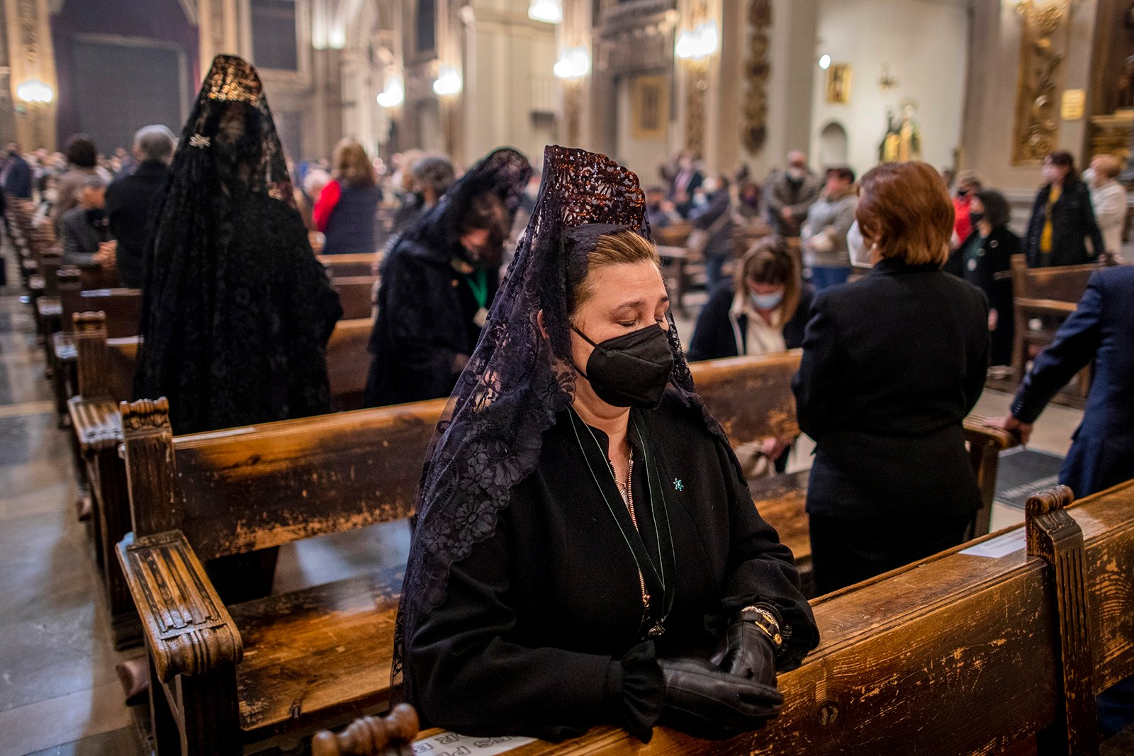 Women wearing traditional 'mantillas' attend a Mass at Collegiate Church of San Isidore in downtown Madrid, Spain, Thursday, April 1, 2021. For a second year running, Spain has had to cancel Easter Week processions to help stop the spread of COVID-19. (AP Photo/Manu Fernandez)