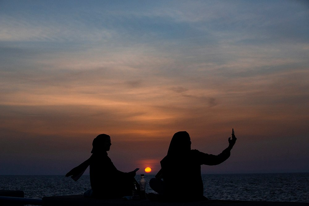 Muslim women pose for a selfie as they wait to break their fast at sundown during the Muslim holy fasting month of Ramadan, along the seaside promenade in Beirut, Lebanon, Thursday, April 15, 2021. Muslims around the world are observing Ramadan, the holiest month in Islamic calendar, when they refrain from eating, drinking, smoking, and sex from dawn to dusk. (AP Photo/Hassan Ammar)