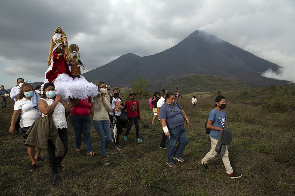 Residents carry statues of the town's patron saint, San Vicente, Jesus, and the Virgin Mary, to pray that the Pacaya Volcano decreases its activity in San Vicente Pacaya, Guatemala, Wednesday, April 21, 2021. Residents of small communities living around Pacaya volcano wake up each morning wondering if the lava from the current eruption will reach their homes. (AP Photo/Moises Castillo)