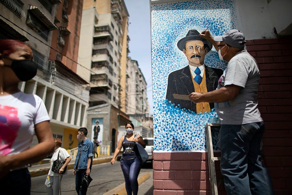 """Artist Mervin Marmol puts the finishing touches on his painting of the late Dr. Jose Gregorio Hernandez at the street corner where he died in a car accident in 1919, in La Pastora neighborhood in Caracas, Venezuela, Monday, April 26, 2021. Known as the """"doctor of the poor,"""" Hernandez is set to be beatified by the Catholic church, a step towards sainthood, on April 30. (AP Photo/Ariana Cubillos)"""