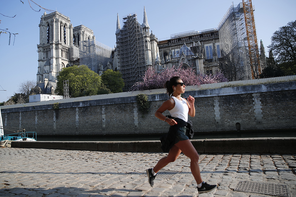 A woman jogs in front of Notre Dame Cathedral, Thursday, April 15, 2021, in Paris. Two years after a fire tore through Paris' most famous cathedral and shocked the world, French President Emmanuel Macron visited the building site that Notre Dame has become to show that French heritage has not been forgotten despite the coronavirus. (AP Photo/Francois Mori)