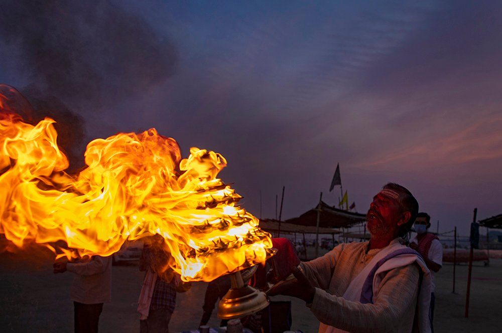 """A Hindu priest rotates a traditional oil lamps in circular movements while performing an evening ritual """"Aarati"""" at Sangam, the confluence of the rivers Ganges and Yamuna, on Ramnavami in Prayagraj, India, Wednesday, April 21, 2021. Ramnavami commemorates the birth of Hindu God lord Rama who is remembered for his prosperous and righteous reign, which has become synonymous with a period of peace and prosperity. (AP Photo/Rajesh Kumar Singh)"""