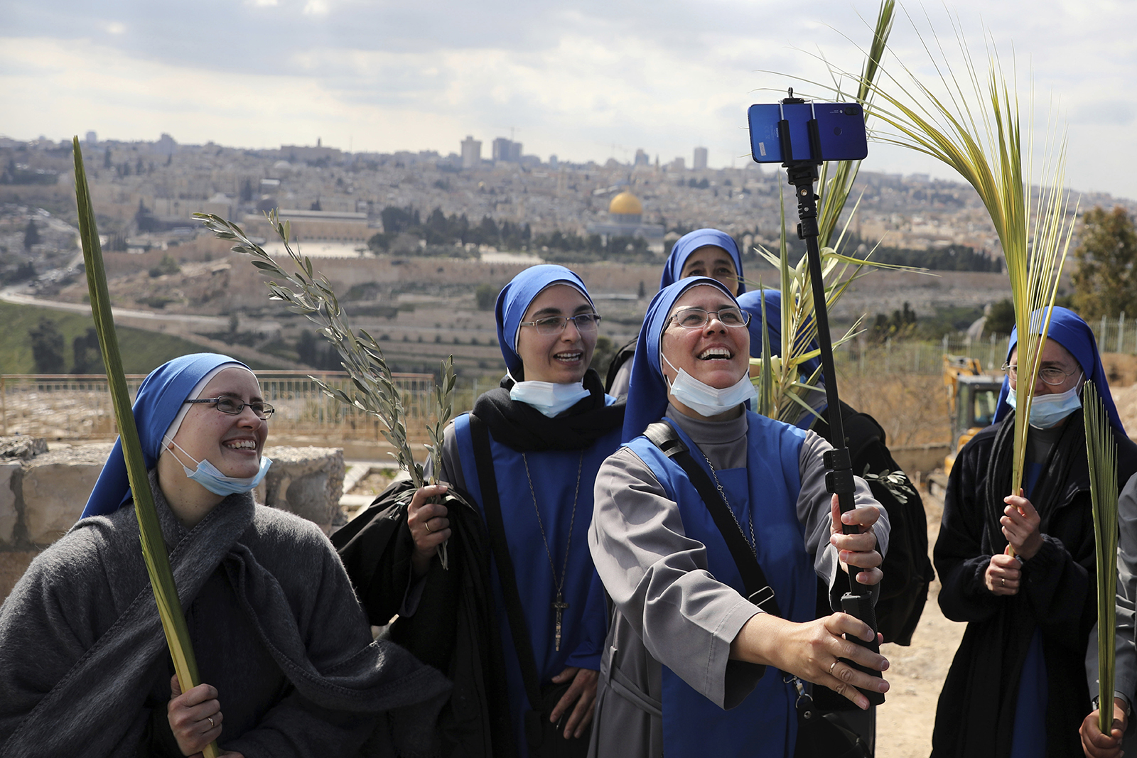Nuns pose for a selfie as they mark Palm Sunday on the Mount of Olives in Jerusalem, Sunday, March 28, 2021. A year after coronavirus restrictions halted mass gatherings, many Christians are celebrating Holy Week together in 2021. (AP Photo/Mahmoud Illean)