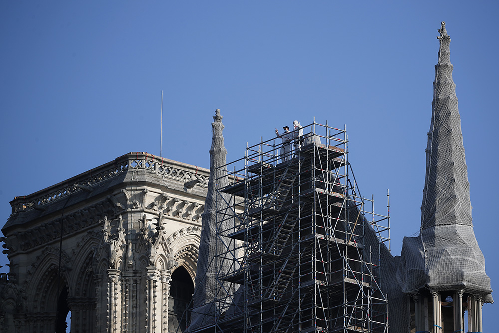 Workers stand atop scaffolding at Notre Dame Cathedral, Thursday, April 15, 2021 in Paris. Two years after a fire tore through Paris' most famous cathedral and shocked the world, French President Emmanuel Macron visited the building site that Notre Dame has become to show that French heritage has not been forgotten despite the coronavirus. (AP Photo/Francois Mori)
