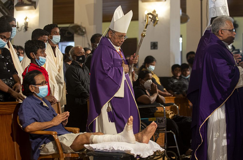 Cardinal Malcolm Ranjith, archbishop of Colombo, center, passes a survivor of the 2019 Easter Sunday attacks as he arrives to conduct a service at St. Anthony's Church in Colombo, Sri Lanka, Wednesday, April 21, 2021. Wednesday marked the second anniversary of the serial blasts that killed 269 people. (AP Photo/Eranga Jayawardena)