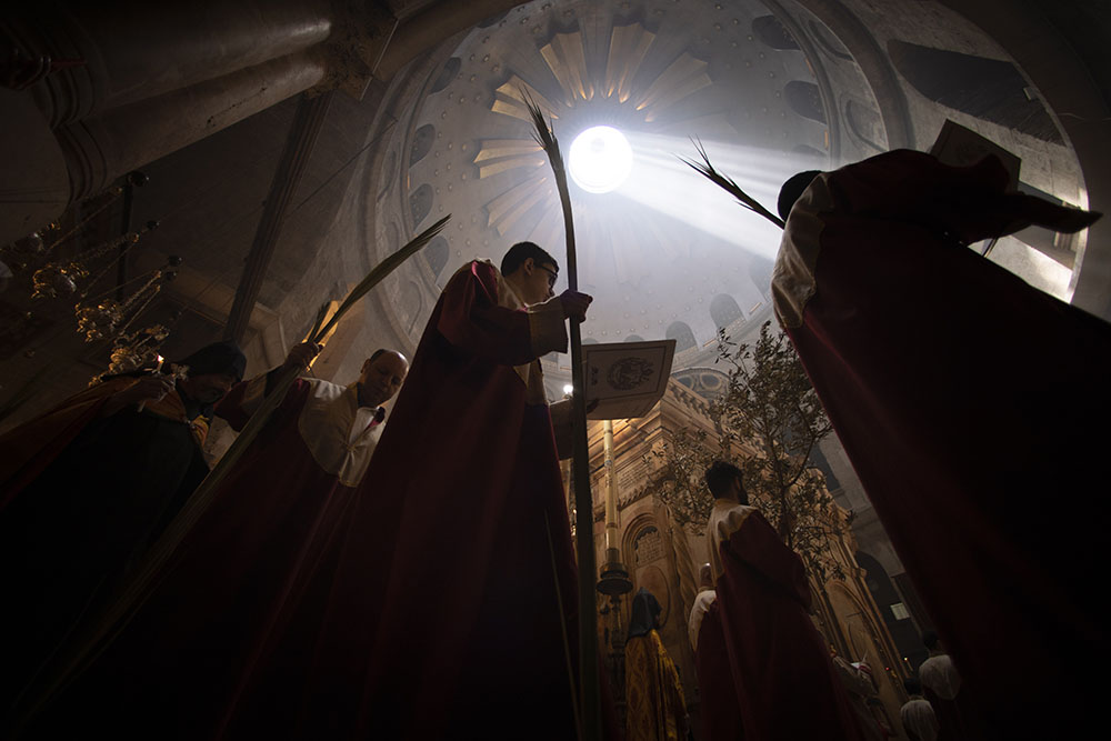 Priests hold palm fronds during the Palm Sunday procession at the Church of the Holy Sepulchre, where many Christians believe Jesus was crucified, buried and rose from the dead, in the Old City of Jerusalem, Sunday, April. 25, 2021. Followers of the Orthodox and Eastern churches began marking Holy Week on Sunday, April 25. (AP Photo/Oded Balilty)