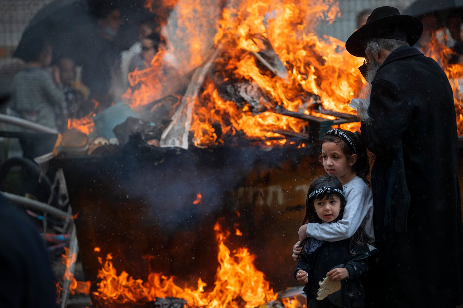 Ultra-Orthodox Jewish men and children burn leavened items in final preparation for the Passover holiday in the ultra-Orthodox Jewish town of Bnei Brak, near Tel Aviv, Israel, Friday, March 26, 2021. Jews are forbidden to eat leavened foodstuffs during the Passover holiday that celebrates the biblical story of the Israelites' escape from slavery and exodus from Egypt. (AP Photo/Oded Balilty)