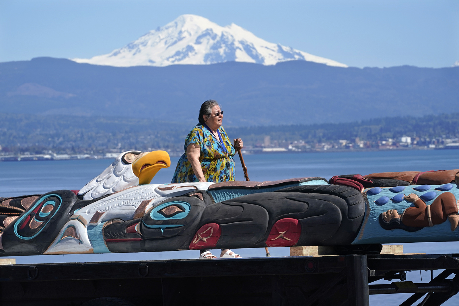 Lummi Nation elder Lucille Spencer prays over a nearly 25-foot totem pole, to be gifted from the tribe to the administration of President Joe Biden, in view of Mount Baker, background, shortly after the pole was moved from a carving shed, Monday, April 19, 2021, on the Lummi Reservation, near Bellingham, Washington. The pole, carved from a 400-year old red cedar, will make a journey from the reservation past sacred indigenous sites, before arriving in Washington, D.C., in early June. Organizers said that the totem pole is a reminder to leaders to honor the rights of Indigenous people and their sacred sites. (AP Photo/Elaine Thompson)