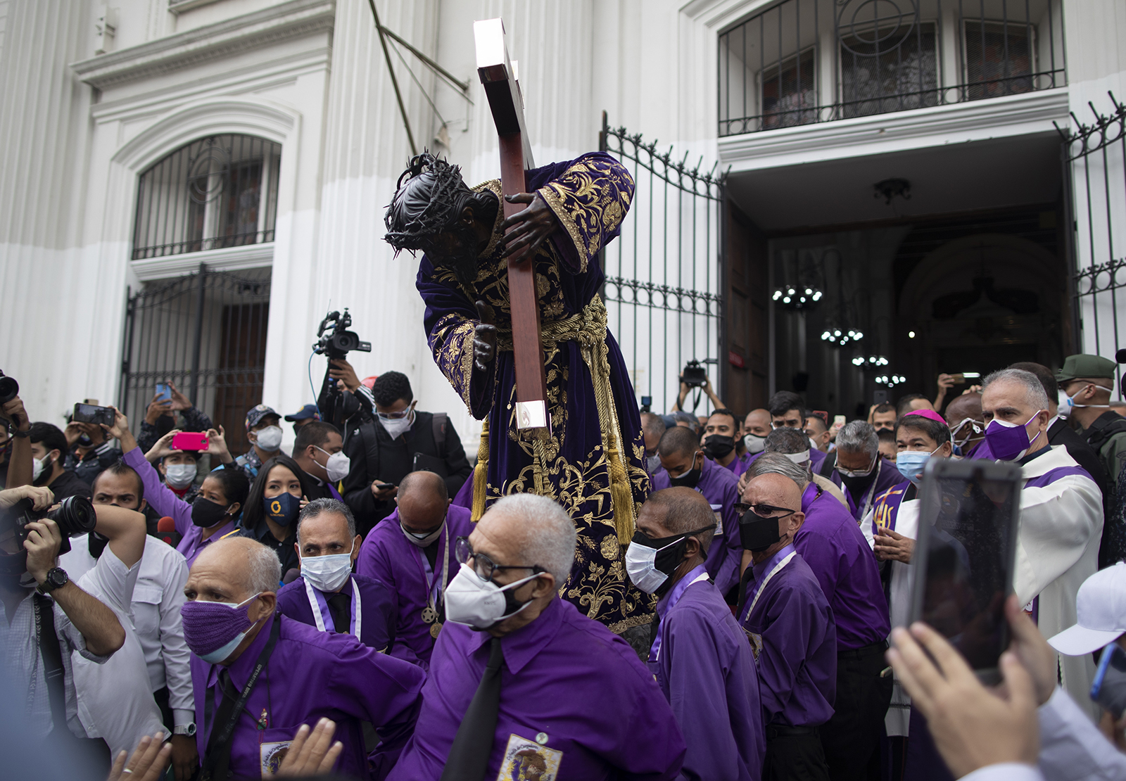 """Men carry the """"Nazareno de San Pablo"""" statue of Jesus from a church to a popemobile for it to be paraded through the neighborhood during Holy Week celebrations amid the COVID-19 pandemic in Caracas, Venezuela, Wednesday, March 31, 2021. The annual procession wasn't allowed for the second year in a row to help contain the spread of the new coronavirus. (AP Photo/Ariana Cubillos)"""
