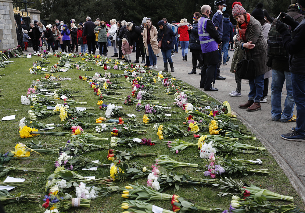 People view flower tributes at Cambridge Gate, at Windsor Castle, one day after the death of Britain's Prince Philip, in Windsor, England, Saturday, April 10, 2021. (AP Photo/Frank Augstein)