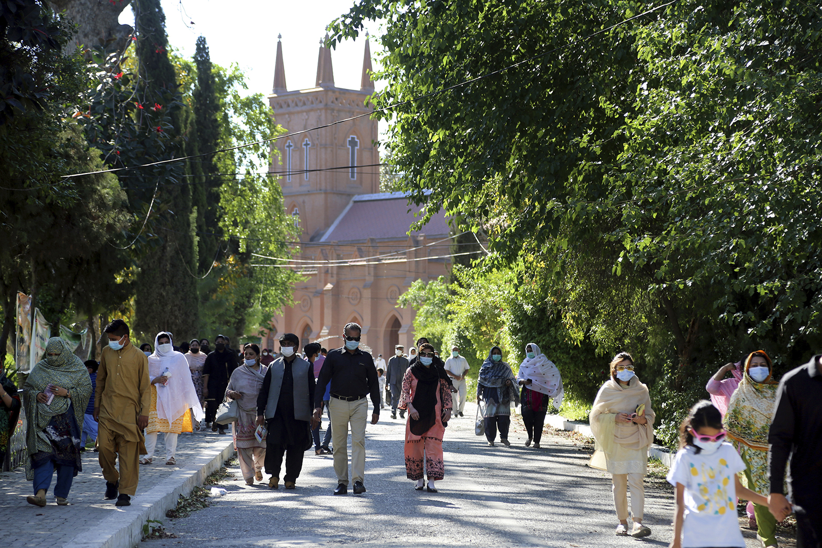 Christian families walk away from St. John's Cathedral after attending Good Friday, in Peshawar, Pakistan, Friday, April 2, 2021. (AP Photo/Muhammad Sajjad)