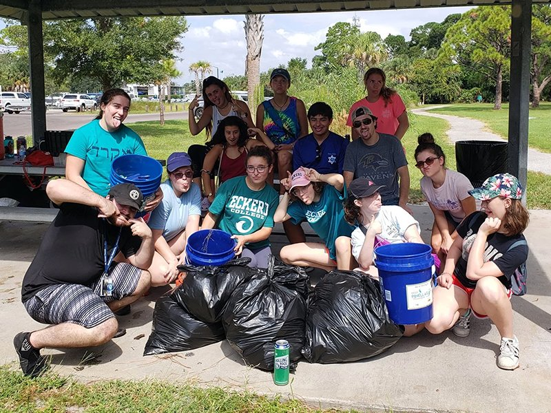 A group poses with their debris cleanup haul during a Reverse Tashlich event in Oct. 2019. Photo via RepairTheSea.org