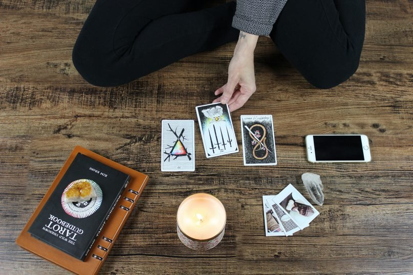 A woman reads her fortune via tarot cards. Photo by Jen Theodore/Unsplash/Creative Commons