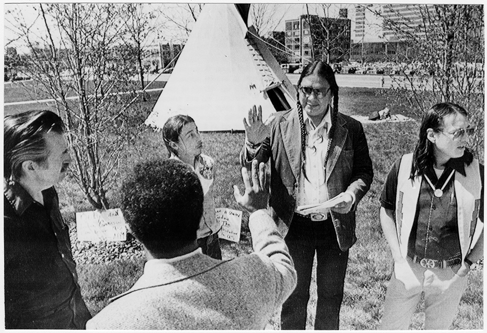 """Native American Indian leaders John Thomas, from right, Mike Haney and Frank Drennon talk to delegates to the United Methodist Church General Conference, seeking their backing for Indian rights, outside the Indianapolis Convention Center on Apr. 23, 1980. Coincidentally, UMCGC participants later adopted a charter for racial justice policies in an interdependent global community. The document, which originated in the church's women's division, has been endorsed by the women's groups in every annual (regional) conference. It asserts that """"the institutional church, despite sporadic attempts to the contrary, also still discriminates,"""" and that """"the racist system in the U.S. today perpetuates the power and control of those of European ancestry."""" The statement also called for support of """"nomination and election processes which include all racial groups employing a quota system until the time that our voluntary performance makes such practice unnecessary."""" RNS archive photo. Photo courtesy of the Presbyterian Historical Society."""