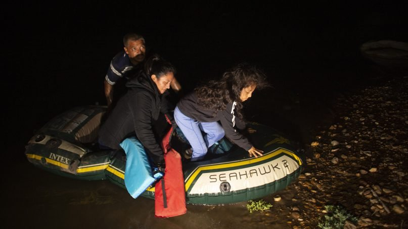 Unaccompanied minor Kaylee Samantha, right, 7, who said she came alone from Mexico, gets off of a small inflatable raft onto U.S. soil after being delivered by a smuggler in Roma, Texas, Wednesday, March 24, 2021. (AP Photo/Dario Lopez-Mills)