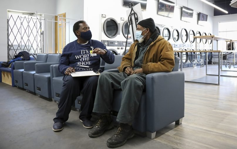 """Herman Simmons, left, makes a vaccination appointment for Theopulis Polk, right, at a Chicago laundromat on March6, 2021. Simmons is a community outreach worker enlisted by St. Anthony Hospital. """"I see myself as my brother's keeper. I don't try to force them. I'm persistent,"""" he said. In a race to boost vaccination rates as COVID-19 variants spread, U.S. communities are working to overcome mistrust and improve access among people of color. (AP Photo/Teresa Crawford)"""