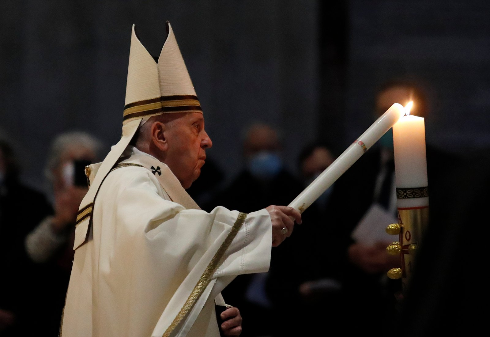 Pope Francis celebrates the Easter Vigil in St. Peter's Basilica as coronavirus pandemic restrictions stay in place for a second year running, at the Vatican, Saturday, April 3, 2021. (Remo Casilli/Pool photo via AP)