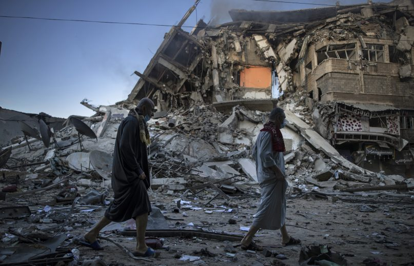 Palestinians walk next to the remains of a destroyed 15 stairs building after being hit by Israeli airstrikes on Gaza City, Thursday, May 13, 2021. (AP Photo/Khalil Hamra)