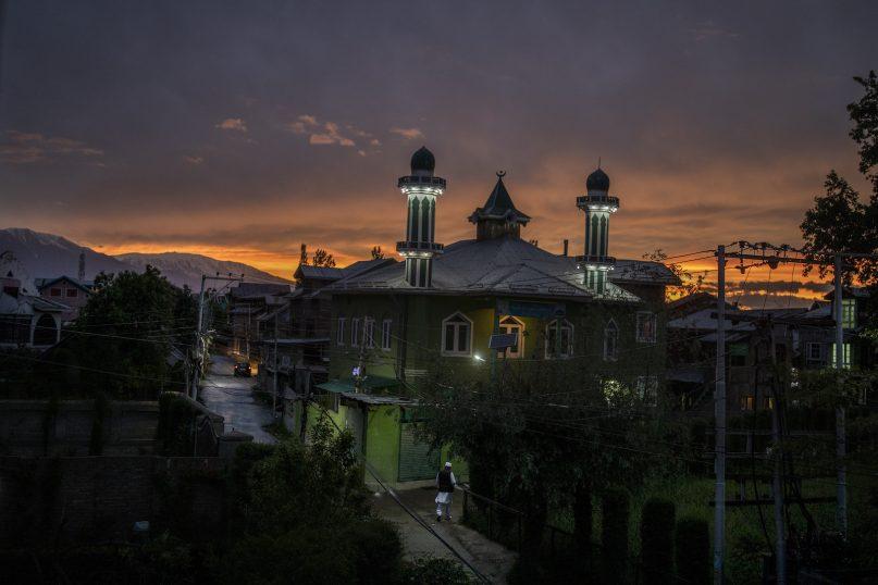 A Kashmiri Muslim walks towards a mosque during sunset in Srinagar, India, Friday, May 14, 2021. (AP Photo/Altaf Qadri)