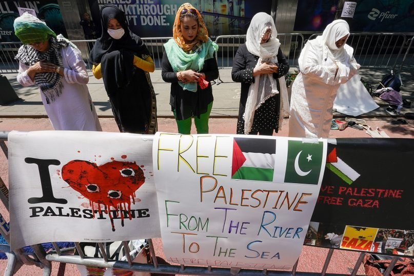Supporters of the Palestinians perform Friday prayers during a demonstration outside the Israeli Consulate in New York on May 21, 2021. A cease-fire has taken effect after 11 days of heavy fighting between Israel and Gaza's militant Hamas rulers that was ignited by protests and clashes in Jerusalem.  (AP Photo/Mary Altaffer)