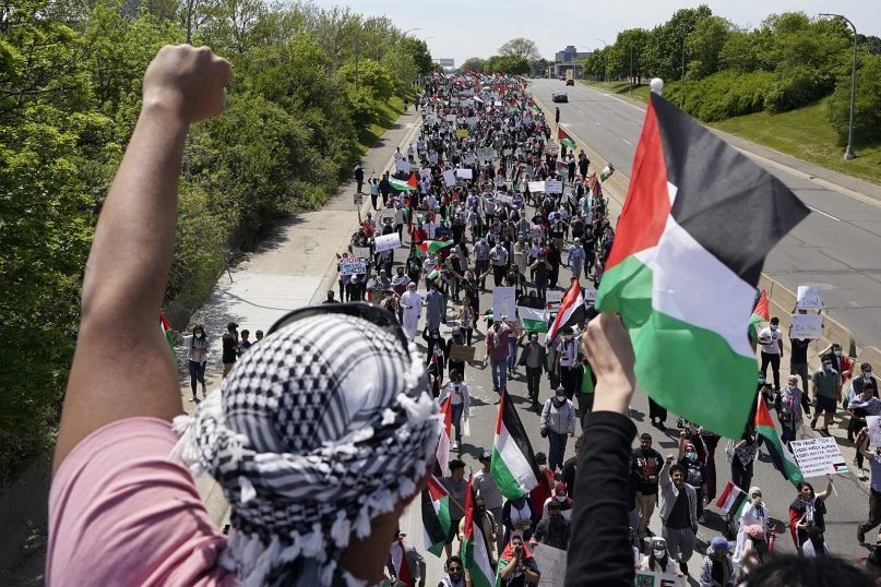 Protesters supporting Palestinians walk down Michigan Avenue, as President Joe Biden visits a Ford electric vehicle center nearby,  May 18, 2021, in Dearborn, Michigan. Biden's efforts to spotlight his big infrastructure plans are suddenly being overshadowed by the escalating violence between Israel and the Palestinians.  (AP Photo/Carlos Osorio)
