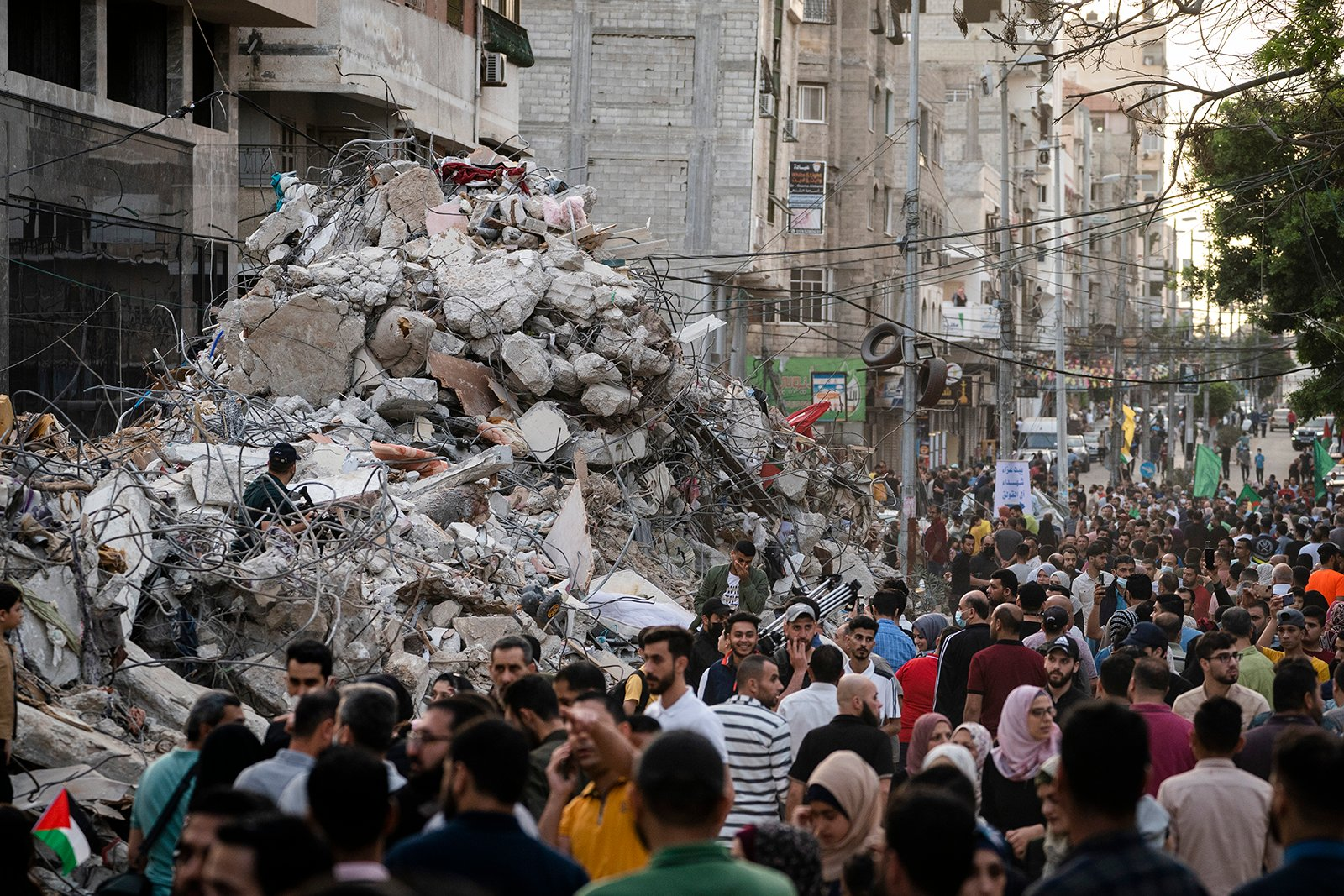 People pass a rubble heap beside a building previously destroyed by an Israeli airstrike, following a cease-fire reached after an 11-day war between Gaza's Hamas rulers and Israel, in Gaza City, Friday, May 21, 2021. (AP Photo/John Minchillo)