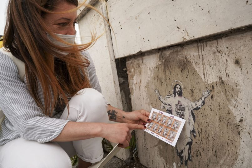 Artist Alessia Babrow holds the Vatican stamps next to her street art during an interview with The Associated Press, at the Vatican, May 14, 2021. One night in early 2019, Rome street artist Babrow glued a stylized image of Christ she had made to a bridge near the Vatican. A year later, she was shocked to learn that the Vatican had used her image, featuring her hallmark heart emblazoned across Christ's chest, as its 2020 Easter postage stamp.  (AP Photo/Andrew Medichini)