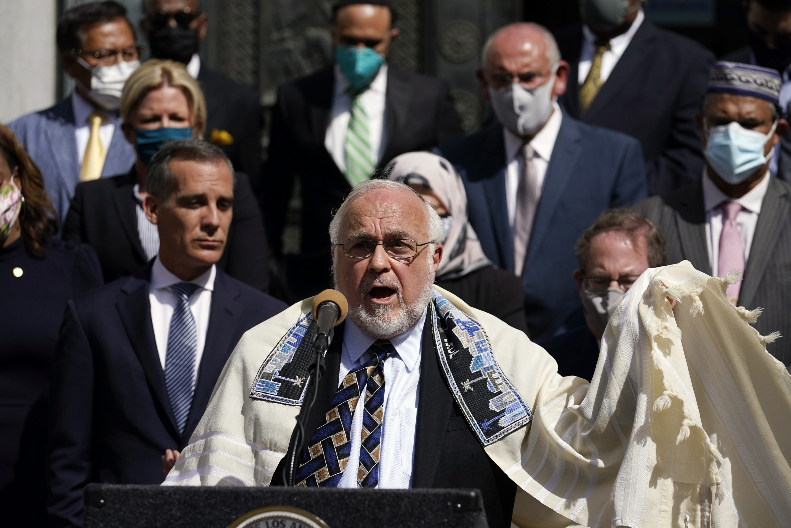 Rabbi Abraham Cooper, center, of the Simon Wiesenthal Center, speaks in front of civic and faith leaders outside City Hall, Thursday, May 20, 2021, in Los Angeles. Faith and community leaders in Los Angeles called for peace, tolerance and unity in the wake of violence in the city that is being investigated as potential hate crimes. (AP Photo/Marcio Jose Sanchez)
