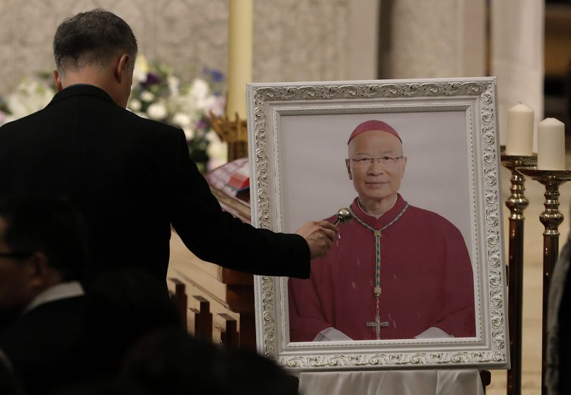 A parishioner pays his last respects in front of the picture of Bishop Michael Yeung at a vigil Mass in Hong Kong, Thursday, Jan. 10, 2019. Hong Kong Catholics mourned the loss of their bishop with a Mass on Thursday night amid a low-key struggle among clergy over reconciliation between the Vatican and Beijing. Bishop Michael Yeung died last week from liver failure after less than two years as the head of the diocese of more than 500,000 Catholics in the semi-autonomous Chinese territory. (AP Photo/Vincent Yu)
