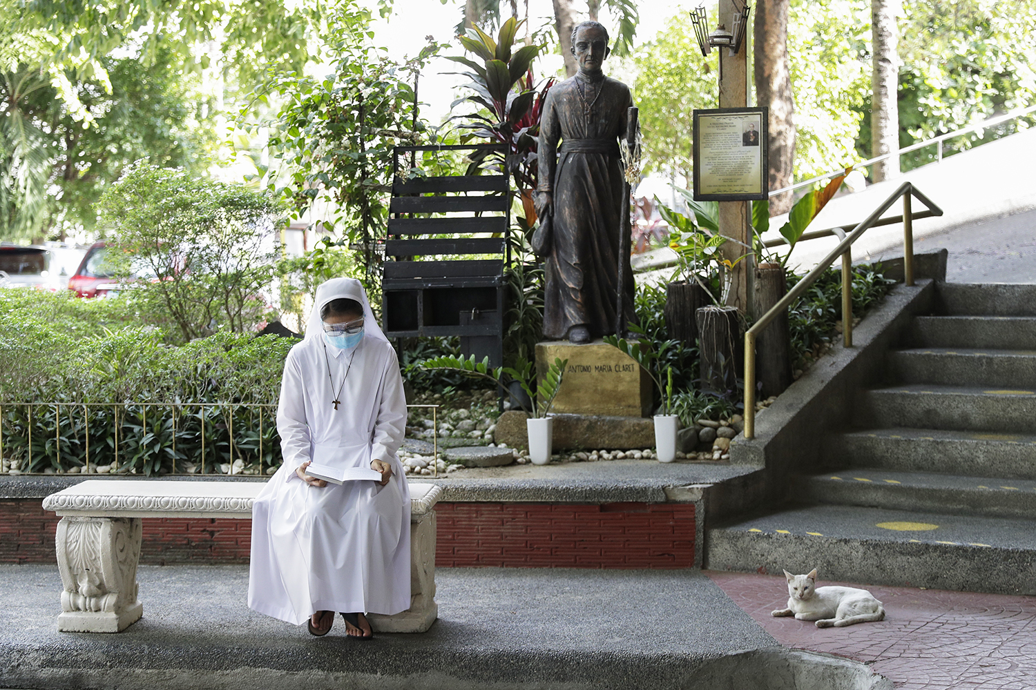 A Catholic nun wearing a protective mask reads outside the Immaculate Heart of Mary Parish Church that turned into a temporary vaccination center in Quezon City, Philippines on Friday, May 21, 2021. Philippine officials have been ordered not to disclose in advance the COVID-19 vaccine brands to be administered in immunization sites after those offering newly arrived Pfizer shots drew big crowds in what could be an indication of public preference for Western vaccines.(AP Photo/Aaron Favila)