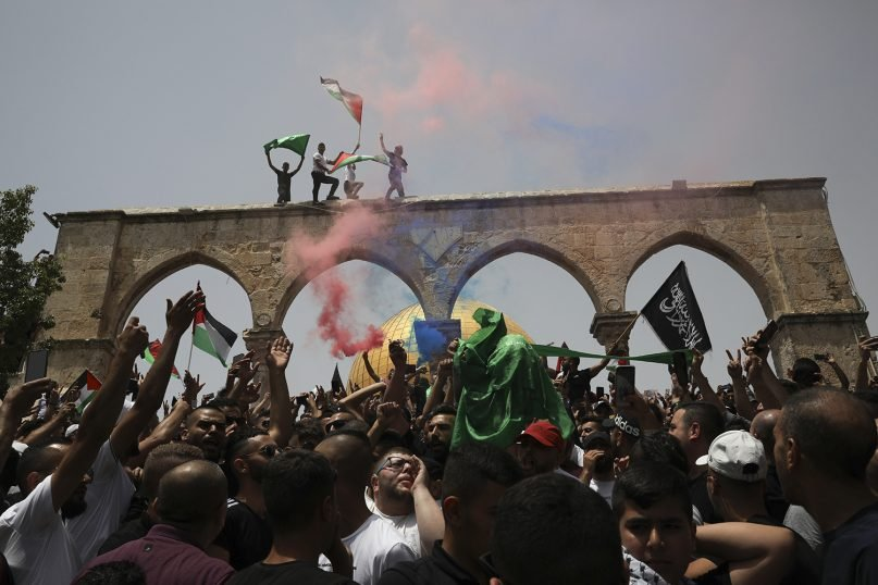 Palestinians wave national flags in front of the Dome of the Rock in the Al-Aqsa Mosque complex in Jerusalem on May 21, 2021, as a cease-fire took effect between Hamas and Israel after an 11-day war. (AP Photo/Mahmoud Illean)