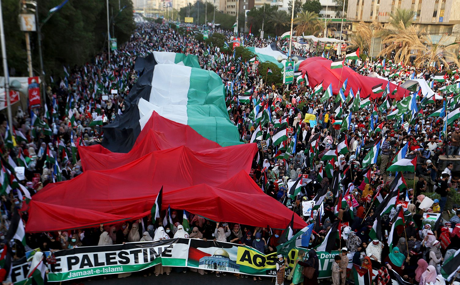 Supporters of the Pakistani religious group, Jamaat-e-Islami, display huge Palestinians flags during a rally in support of Palestinians, in Karachi, Pakistan, Sunday, May 23, 2021. (AP Photo/Fareed Khan)