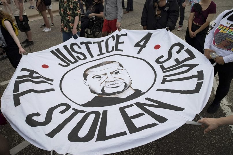 People hold a banner at a rally and march organized by families who were victims of police brutality for the one year anniversary of George Floyd's death on Monday, May 24, 2021, in St. Paul, Minn. (AP Photo/Christian Monterrosa)