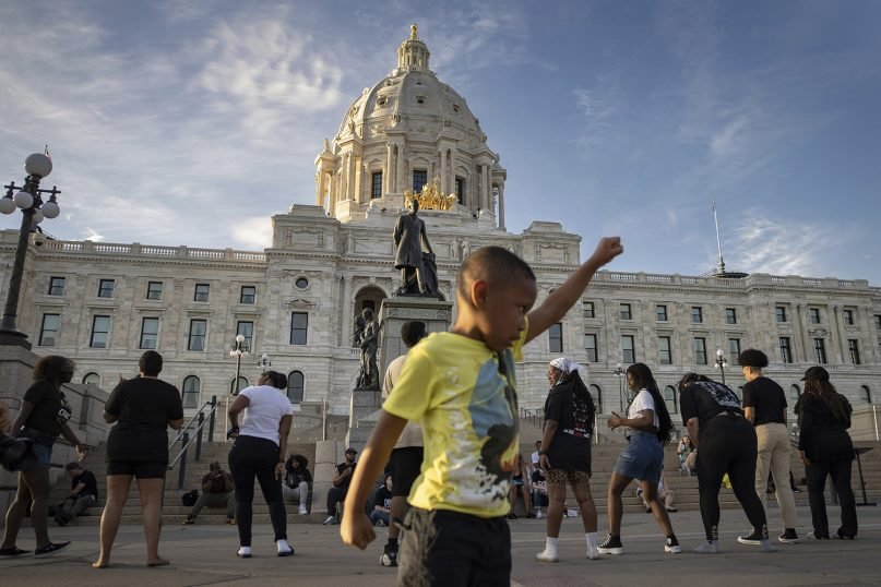 A young boy holds his fist up as people dance at a rally and march May 24, 2021, in St. Paul, Minnesota, organized by families who were victims of police brutality. The event marked the one-year anniversary of George Floyd's death. (AP Photo/Christian Monterrosa)