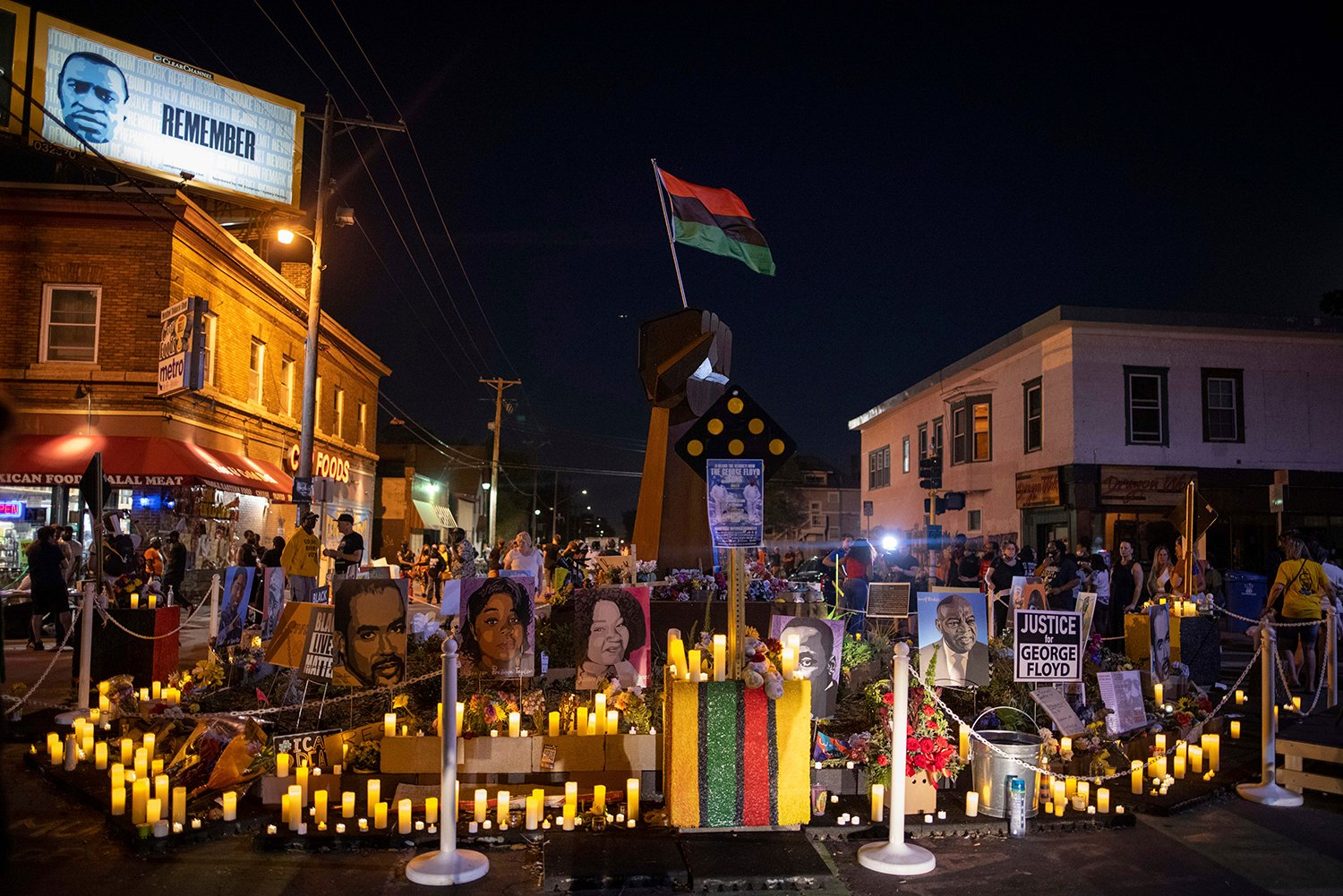 Community members place candles around the iron fist at 38th Street and Chicago Avenue--informally known as George Floyd Square--on the one-year anniversary of George Floyd's death, Tuesday, May 25, 2021, in Minneapolis. (AP Photo/Christian Monterrosa)