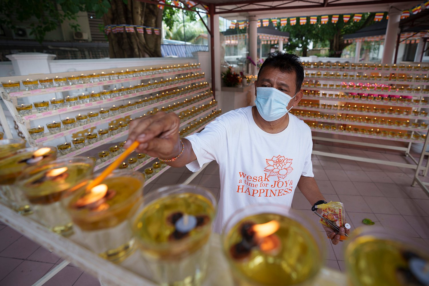 A man wearing a face mask lights up a candle from oil lamp before offering prayers during Wesak Day at a temple in Kuala Lumpur, Malaysia, Wednesday, May 26, 2021. Malaysia's latest coronavirus surge has been taking a turn for the worse as surging numbers and deaths have caused alarm among health officials, while cemeteries in the capital are dealing with an increasing number of deaths. (AP Photo/Vincent Thian)