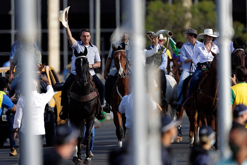 """Brazil's President Jair Bolsonaro, left, arrives on a horse to acknowledge members of the agribusiness community who had gathered to show him their support, in Brasilia, Brazil, Saturday, May 15, 2021. Tightened public health measures remain anathema to Bolsonaro; he has called lockdown measures """"absurd"""". (AP Photo/Eraldo Peres)"""