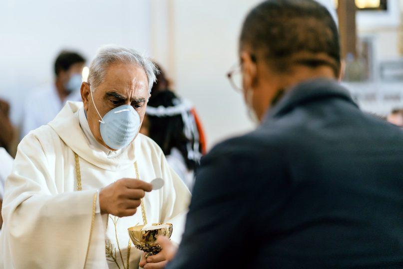 A Catholic priest offers Holy Communion. Photo by Gabriella Clare Marino/Unsplash/Creative Commons