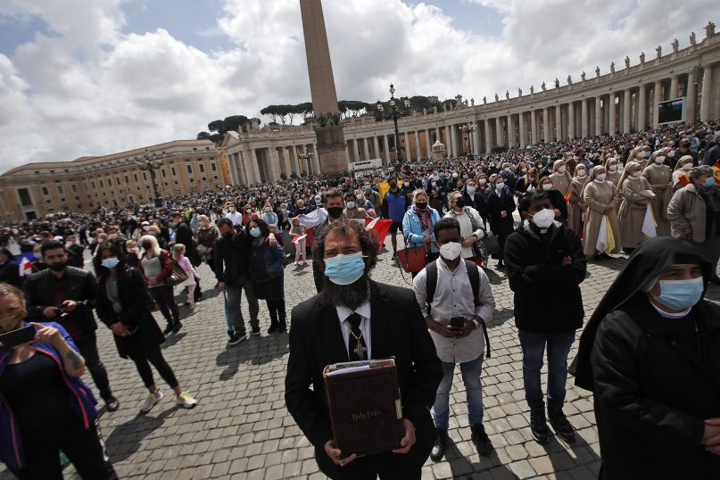 Faithful listen to Pope Francis deliver his message during the Regina Caeli noon prayer from the window of his studio overlooking St. Peter's Square, at the Vatican, Sunday, May 2, 2021. (AP Photo/Alessandra Tarantino)
