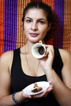 Ani Kalafian, an Armenian American practitioner, holds up a cup and saucer covered in the dregs of an Armenian-style cup of coffee, used in traditional divination. Photo by Sasha Sheldon, courtesy Ani Kalafian