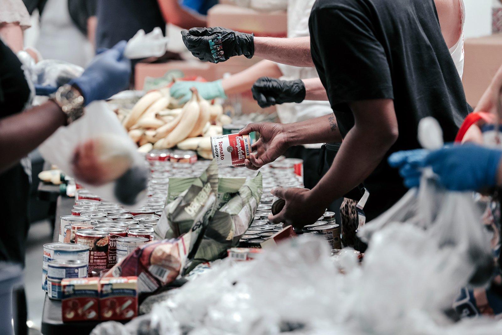 Community members work together organizing food donations. Photo by Joel Muniz/Unsplash/Creative Commons