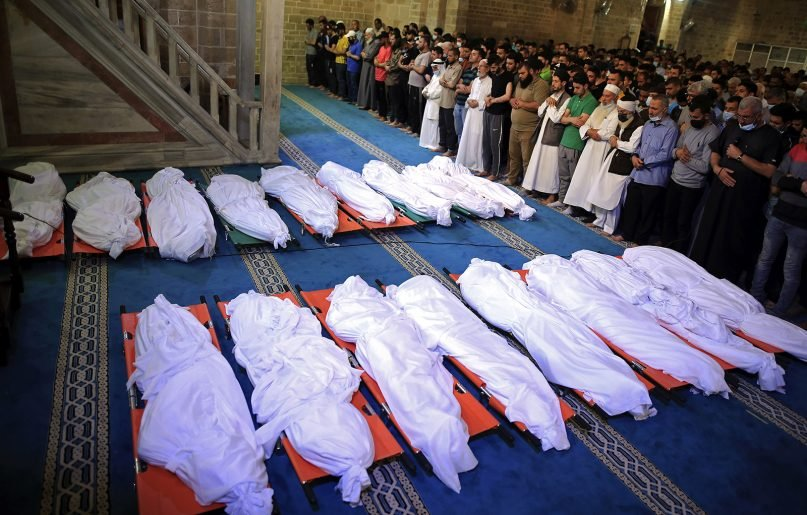 Mourners pray over the bodies of 17 Palestinians who were killed in overnight Israeli airstrikes in Gaza City, May 16, 2021. (AP Photo/Sanad Latifa)