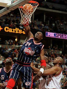 In this Jan. 28, 2000, file photo, Houston Rockets center Hakeem Olajuwon dunks the ball over Denver Nuggets center Popeye Jones during an NBA basketball game in Denver. (AP Photo/David Zalubowski, File)