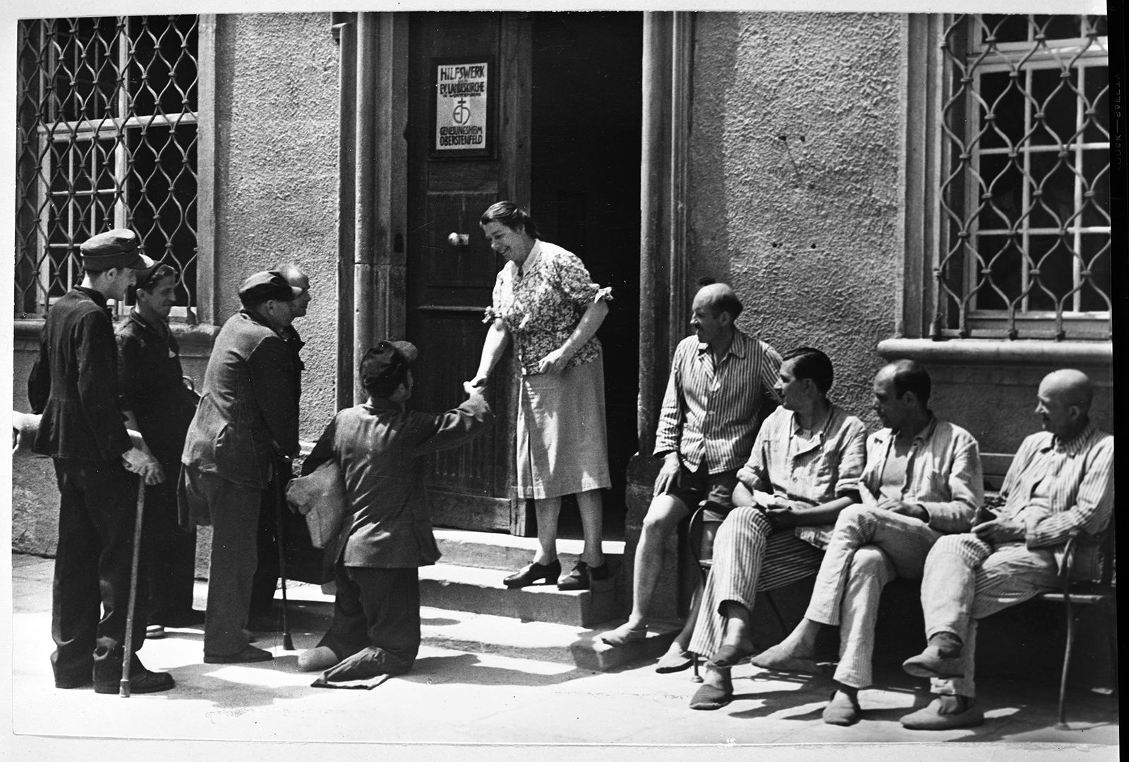 A Hilfswerk worker, center, welcomes disabled German war veterans to a home operated by the Protestant Relief Agency in Oberstenfeld, Germany, located in the American zone, circa 1948. RNS archive photo. Photo courtesy of the Presbyterian Historical Society.