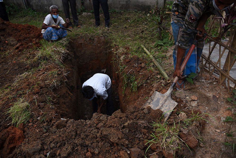 Workers digging as they prepare to bury the body of a person who died of COVID-19 in Guwahati, Assam, India, on April 26, 2021. (Photo by David Talukdar/NurPhoto via Getty Images)