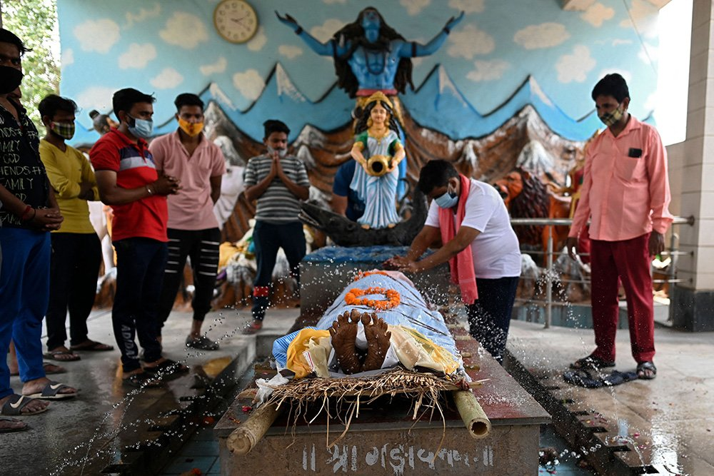 Family members perform rituals at a crematorium for a person who died of the coronavirus in Ghazipur, India, on May 1, 2021. (Photo by Sajjad Hussain/AFP via Getty Images)